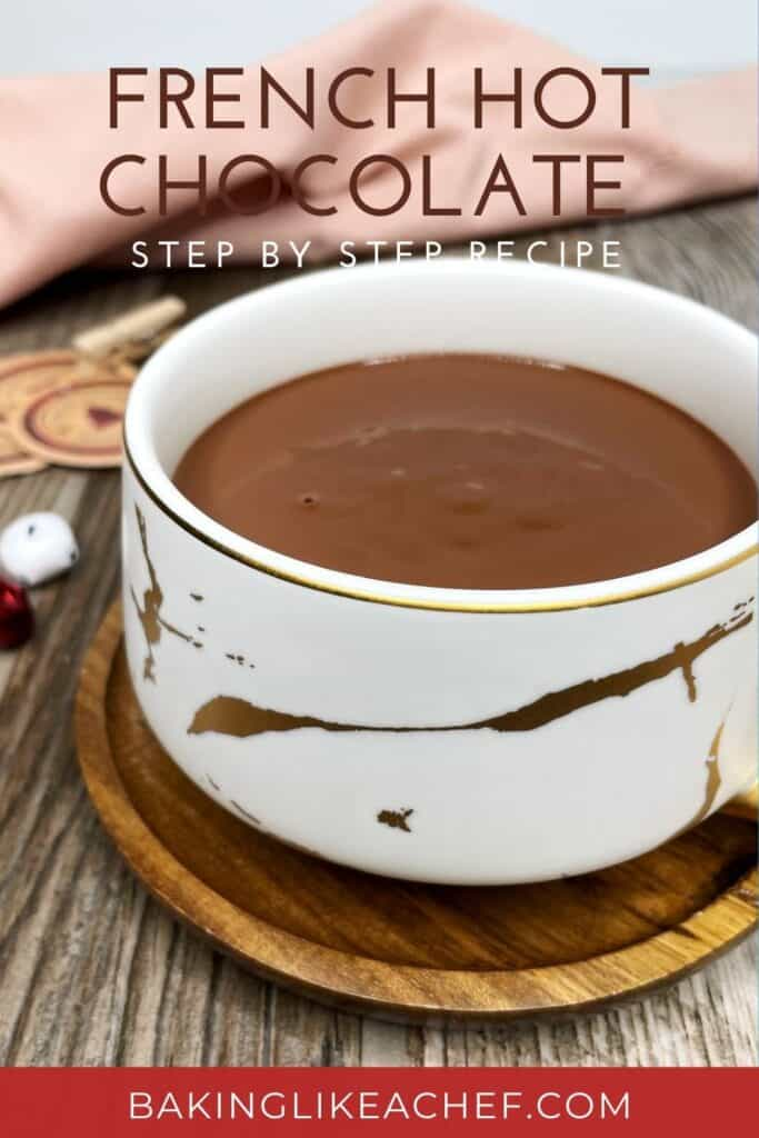 A white cup with chocolat chaud, decorations, and a towel in the background: Pin with text