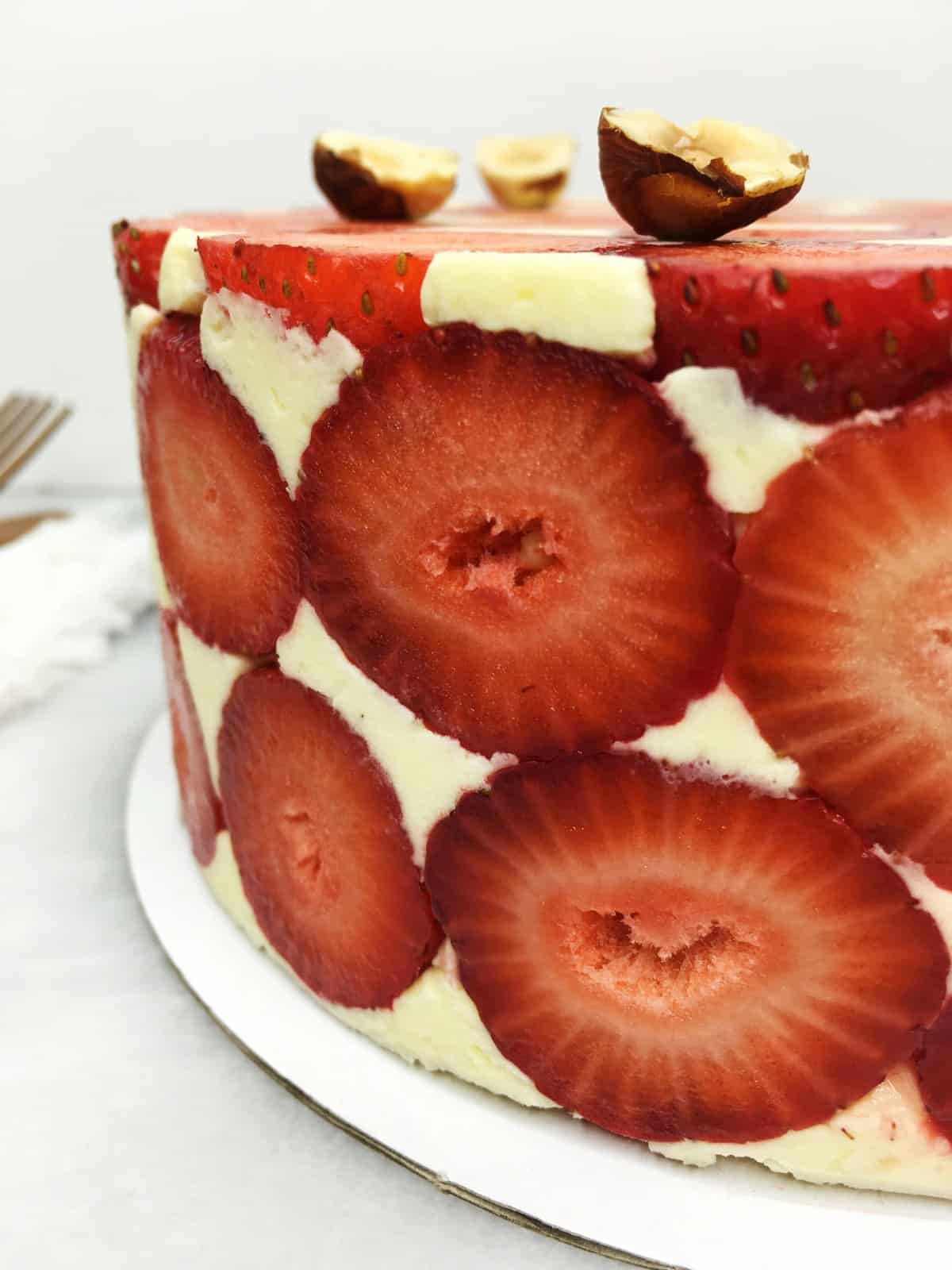 Fraisier cake garnished with fresh strawberries and halves of hazelnuts