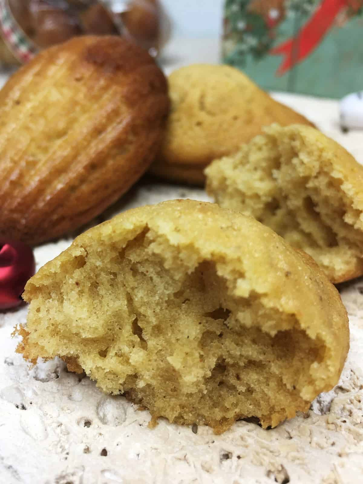 Cut gingerbread madeleine with other spicy madeleines and a Christmas gift box in the background