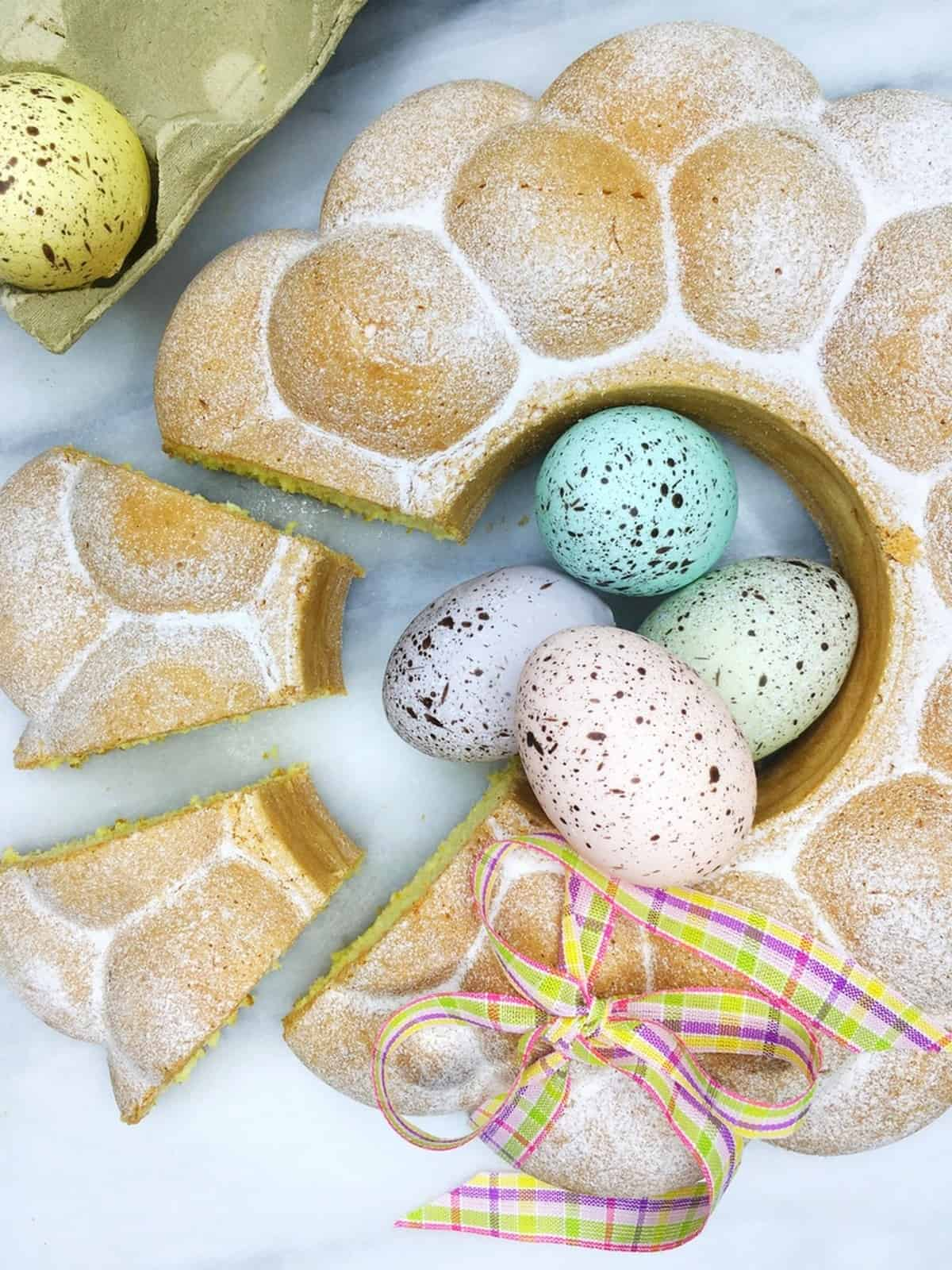 Sliced Savoy cake with decorated Easter eggs: Overhead view