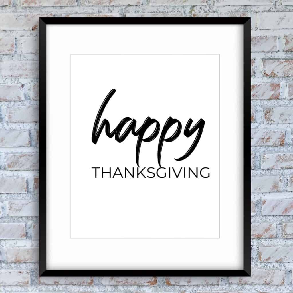 Black frame on the brick wall with the text: Happy thanksgiving
