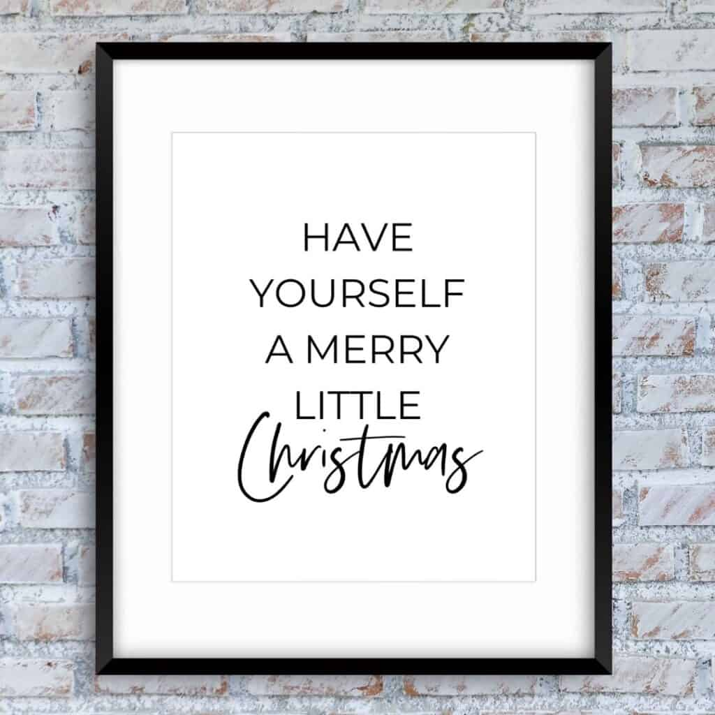 Black frame on the brick wall with the text: Have yourself a merry little Christmas
