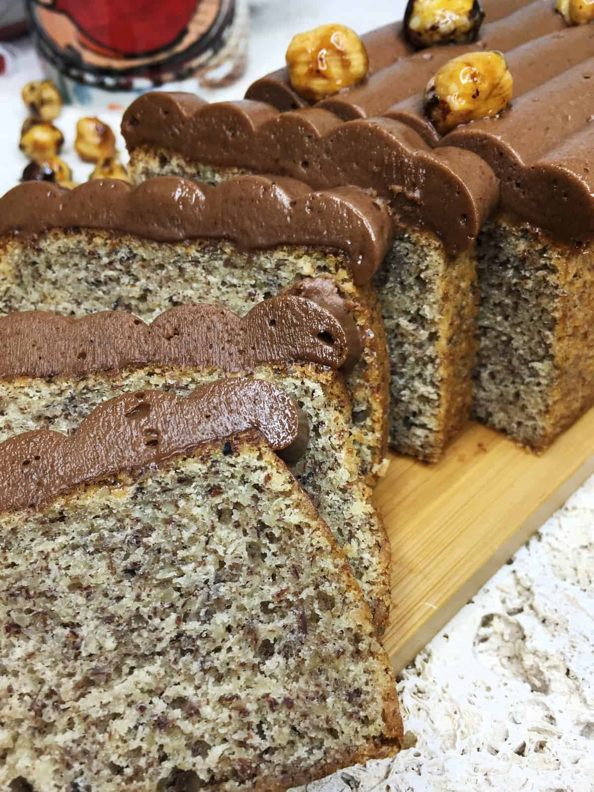A few slices of hazelnut cake on a cutting board and a cup on background
