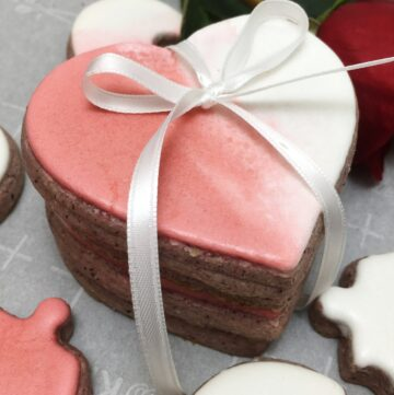Stacked and tied royal icing Valentine's heart cookies with a rose in the background