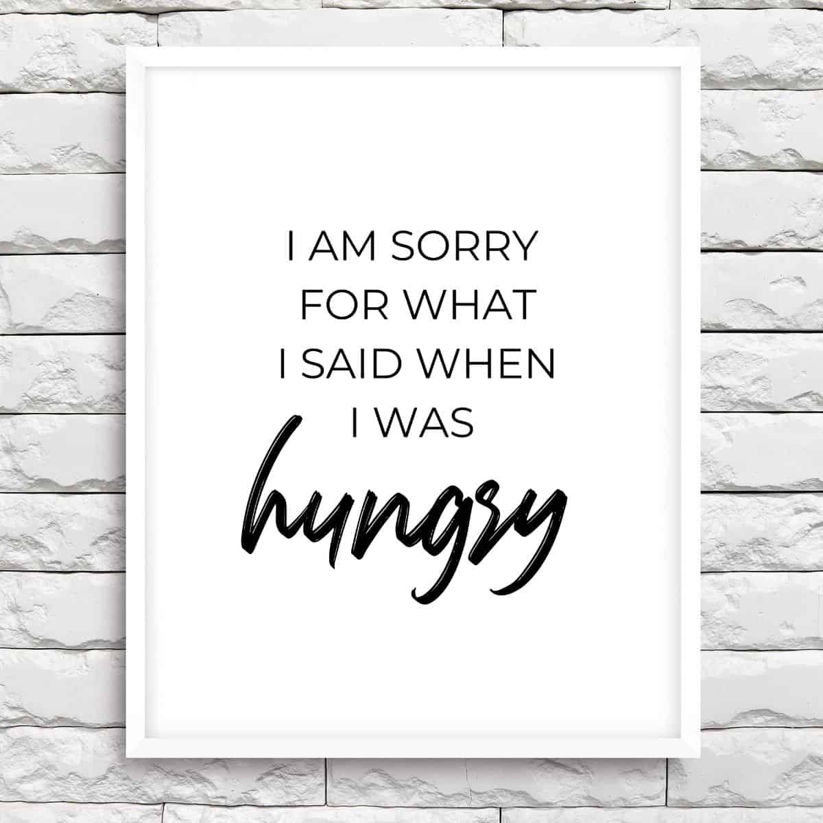 White frame on the brick wall with the text: I am sorry for what I said when I was hungry