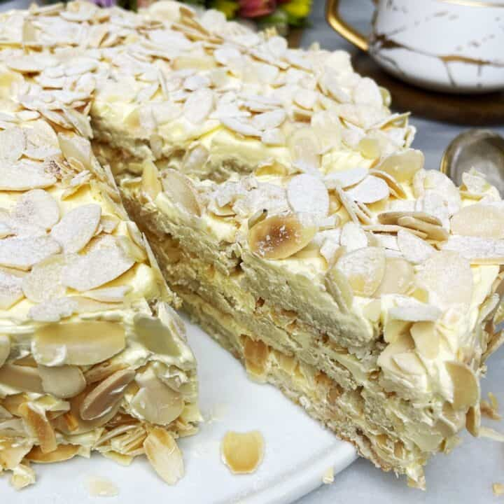 Sliced almond cake covered with flaked almonds on a white platter