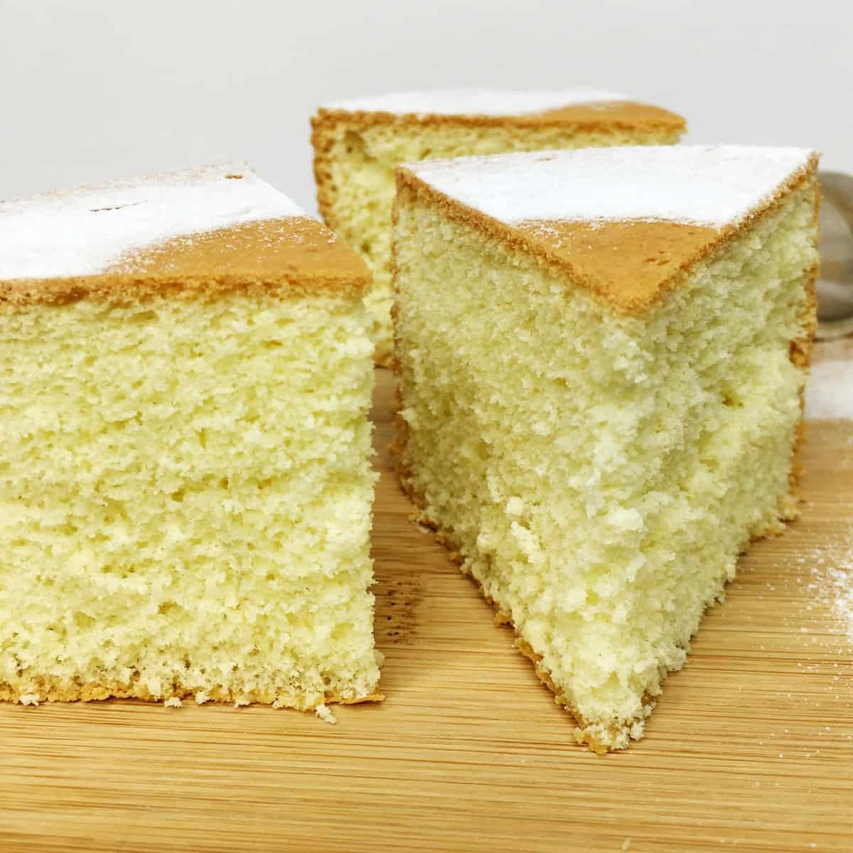 Three slices of sponge cake on a wooden board