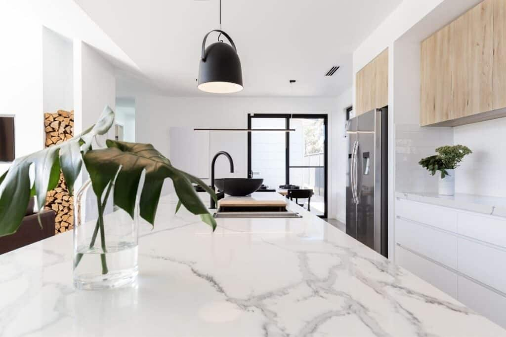 White kitchen with marble island with a plant in a vase