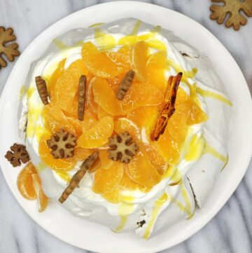 Pavlova dessert topped with mandarin pieces, cookies, and caramel decorations on a plate