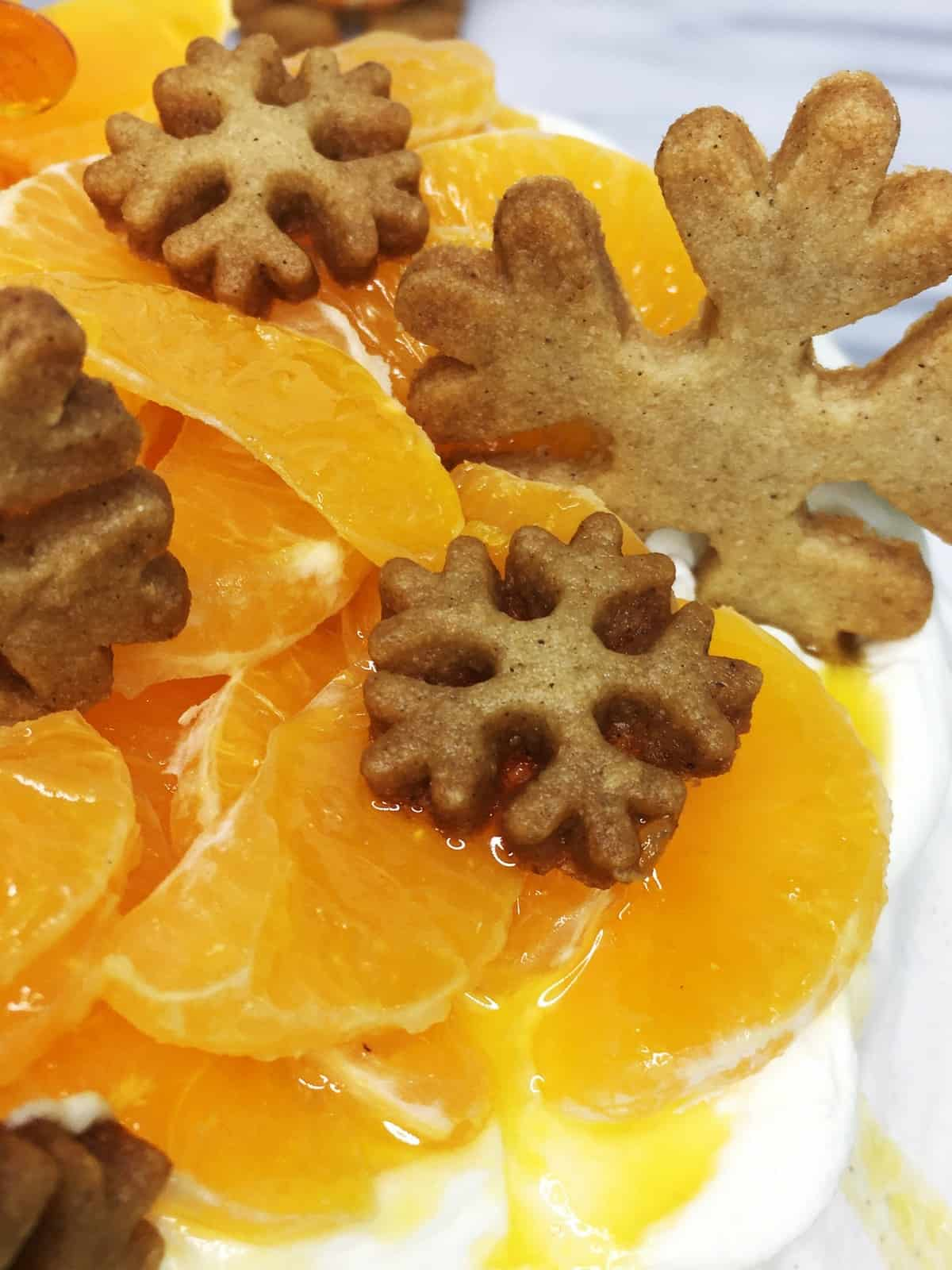 Pavlova cake decorated with mandarin and gingerbread snowflake cookies: Close up