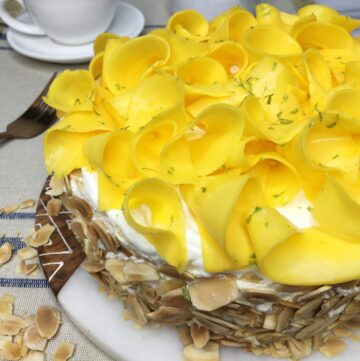 Cake decorated with mango curls on a marble board with white dishes in the background