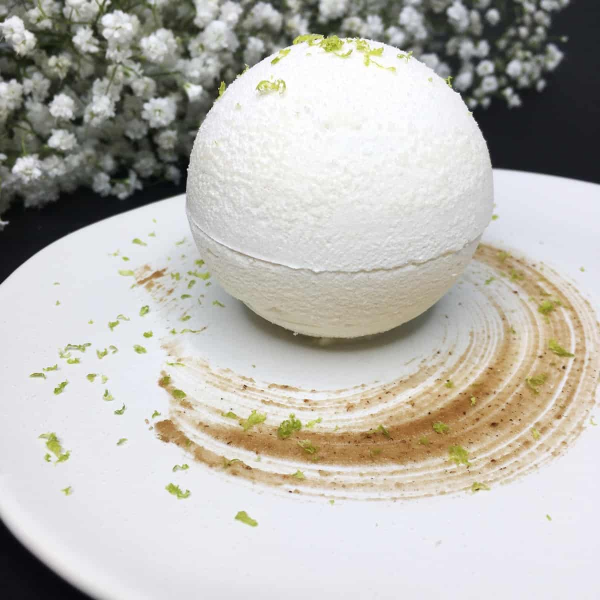 A single meringue ball served on a white plate with flowers aside