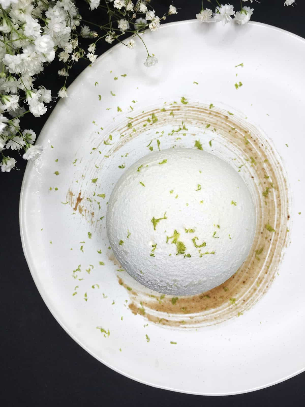 A meringue snowball sprinkled with lime zest on a plate with flowers aside