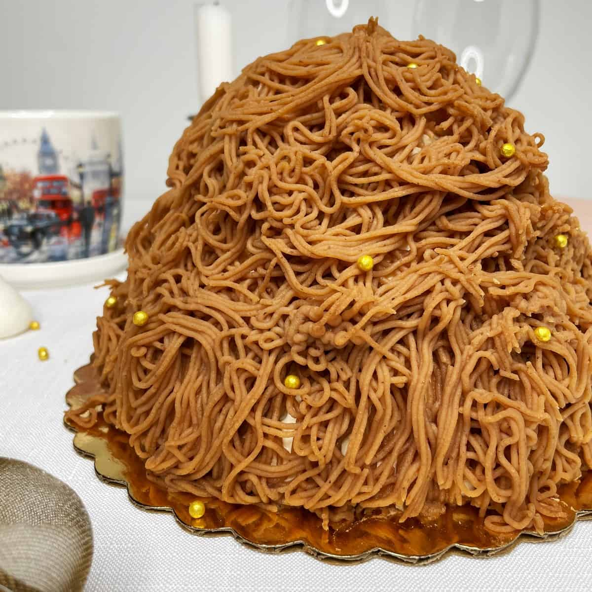 Mont Blanc cake covered with chestnut vermicelli with a cup, a candle, glasses on a table