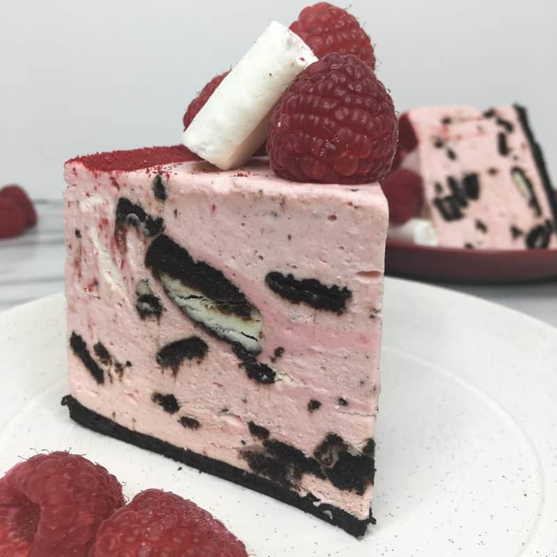 A slice of Raspberry Oreo cheesecake with raspberries on a white plate: Oblique view