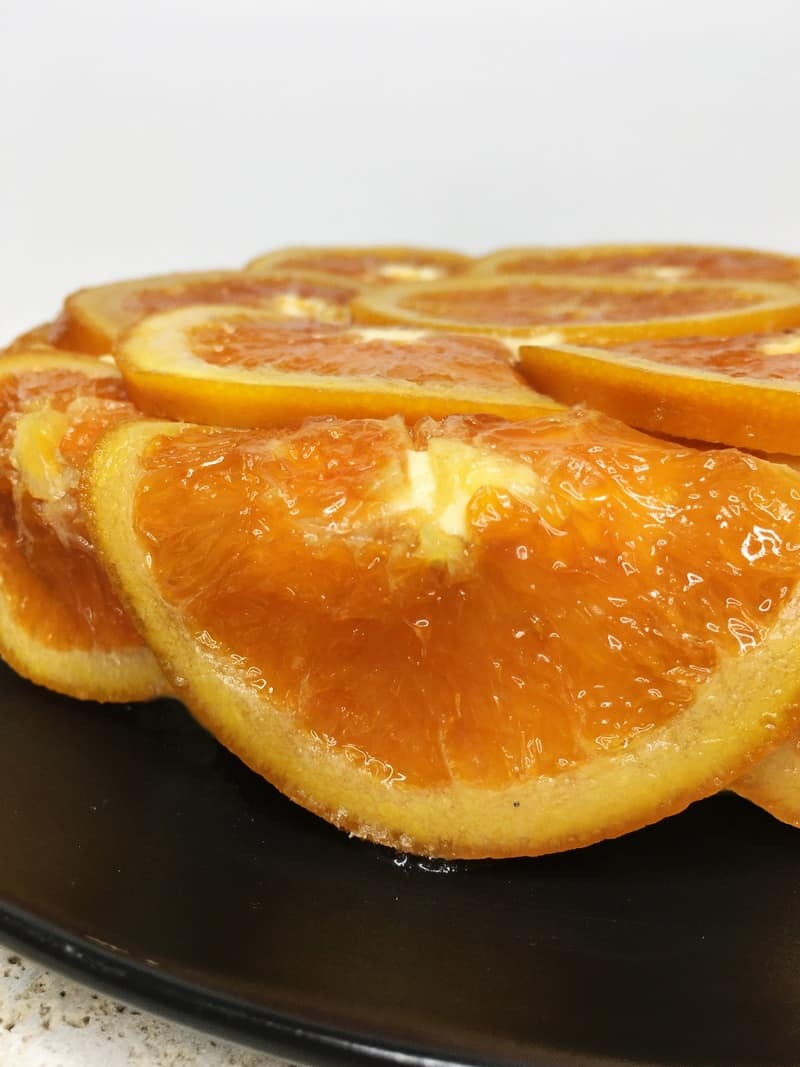 Cake covered with candied oranges on a black plate: Close up