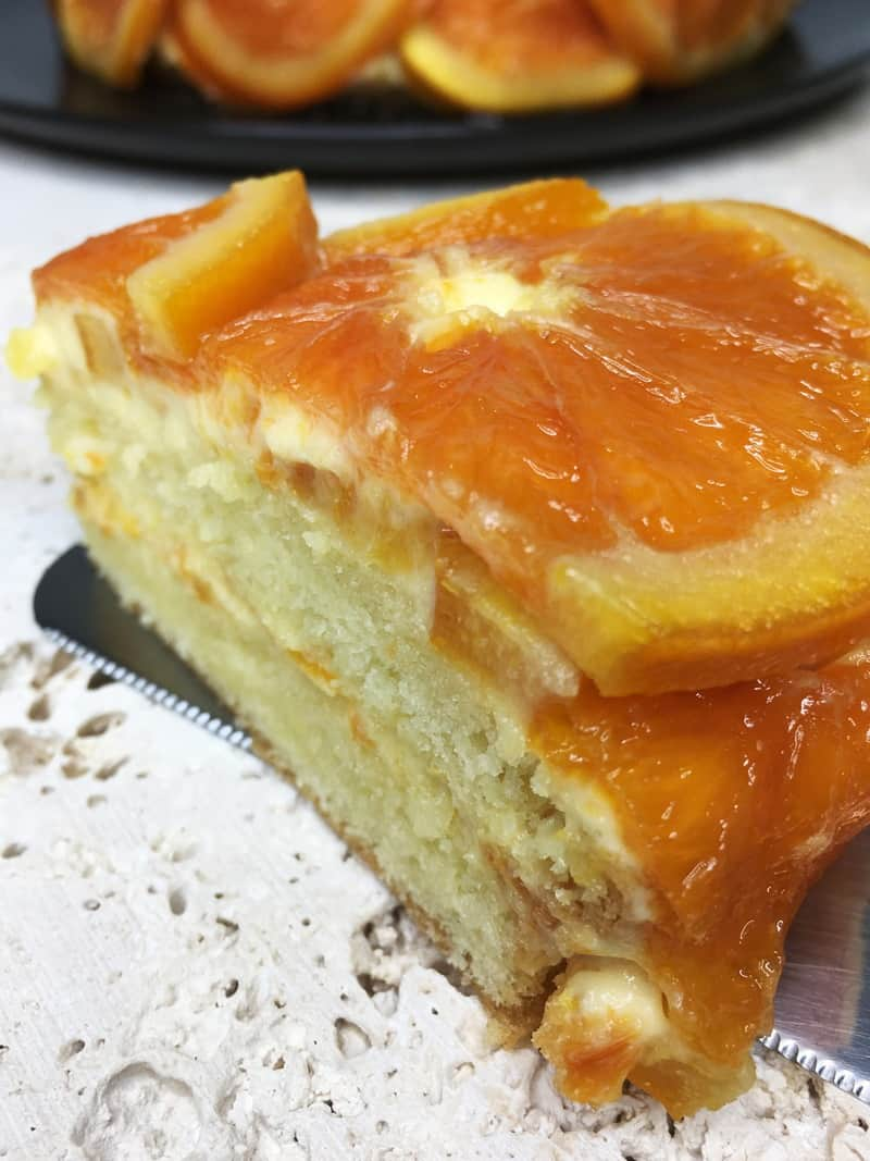 A slice of orange upside-down cake on a board with the rest of the cake on background
