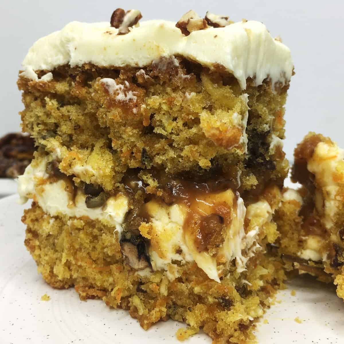 A single slice of carrot cake with pecans and caramel between the cake layers: Close up
