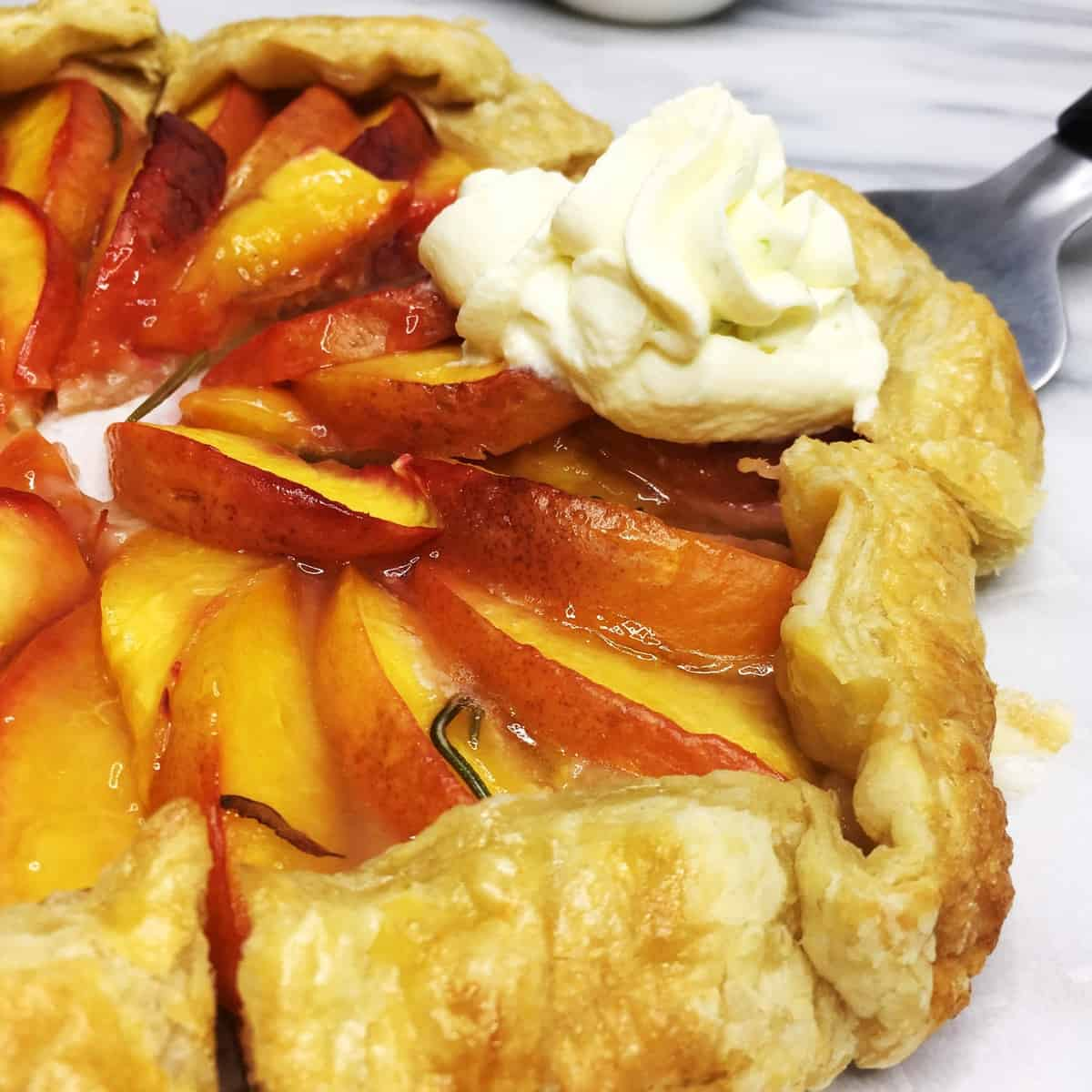 Puff pastry peach galette cut into pieces with one slice topped with the whipped cream