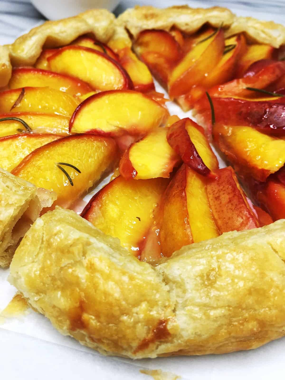 Peach galette cut into pieces on a marble board