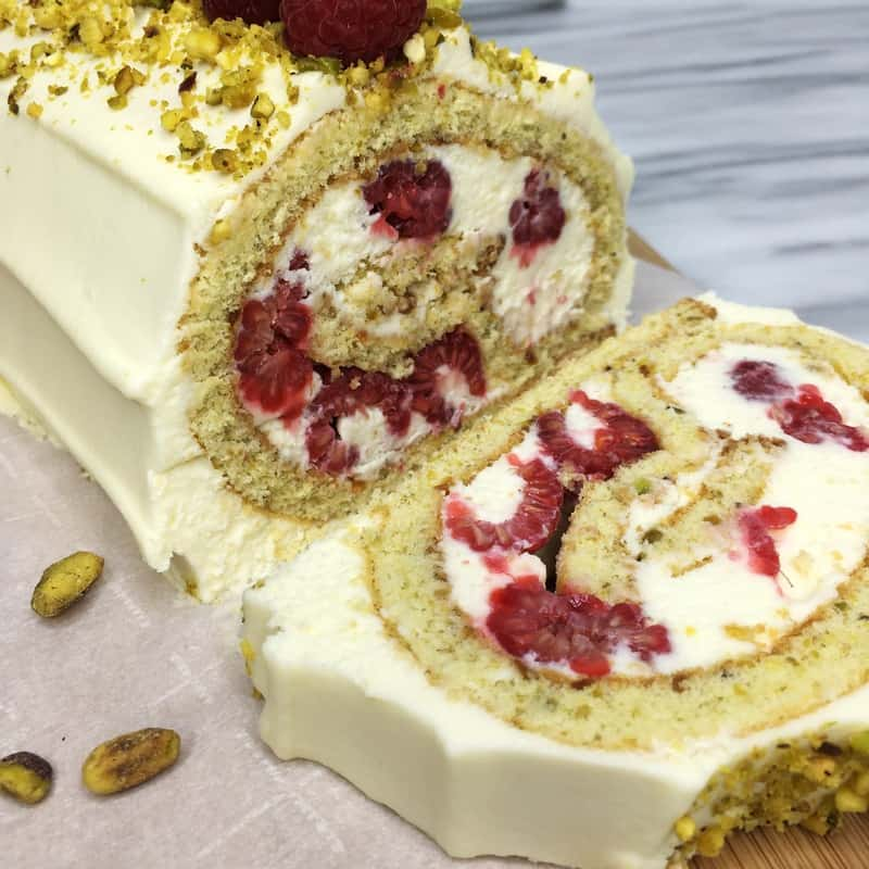 A slice of Raspberry Pistachio Roulade with a whole cake: Close up