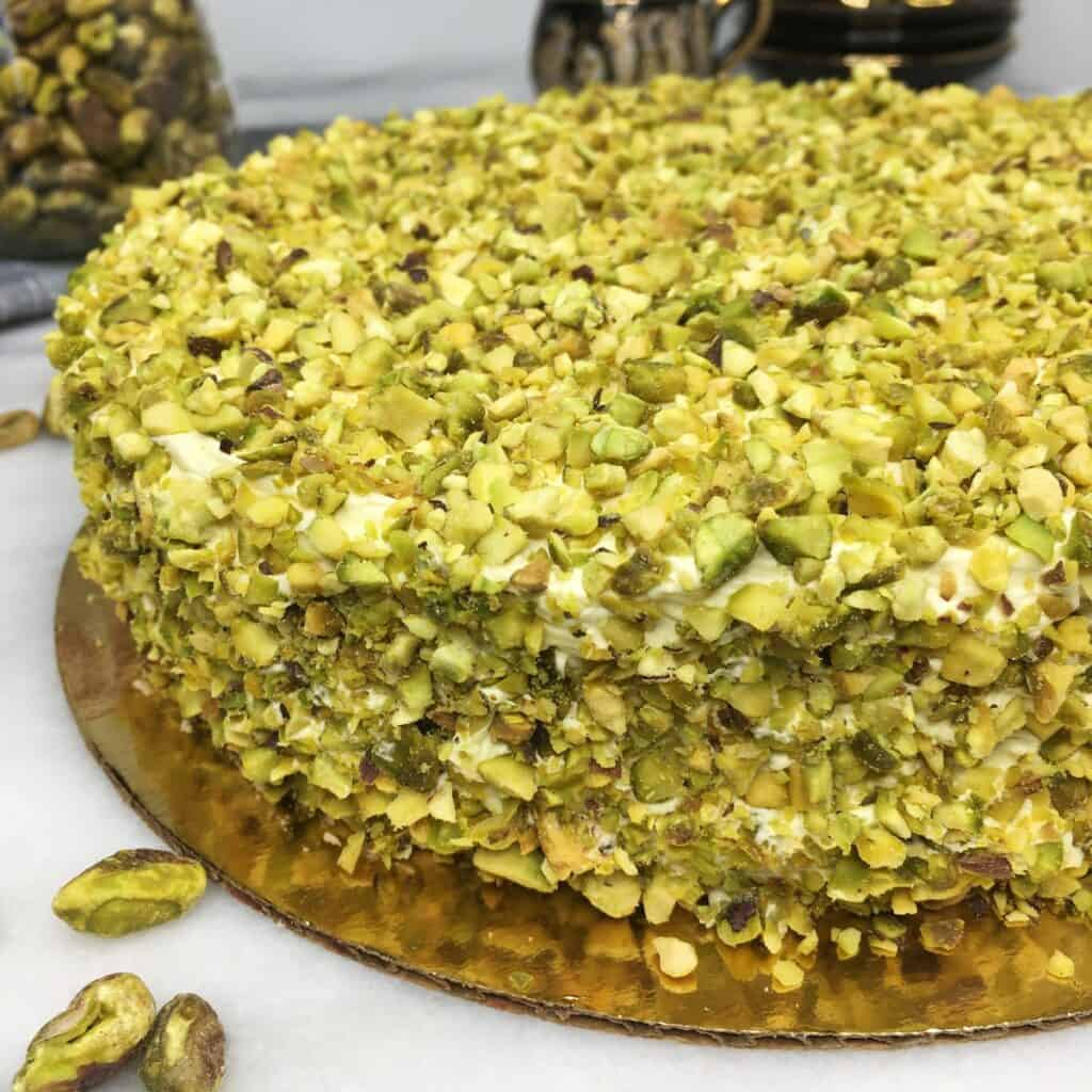 Pistachio Sans Rival cake in a golden cake board with nuts and cups on background