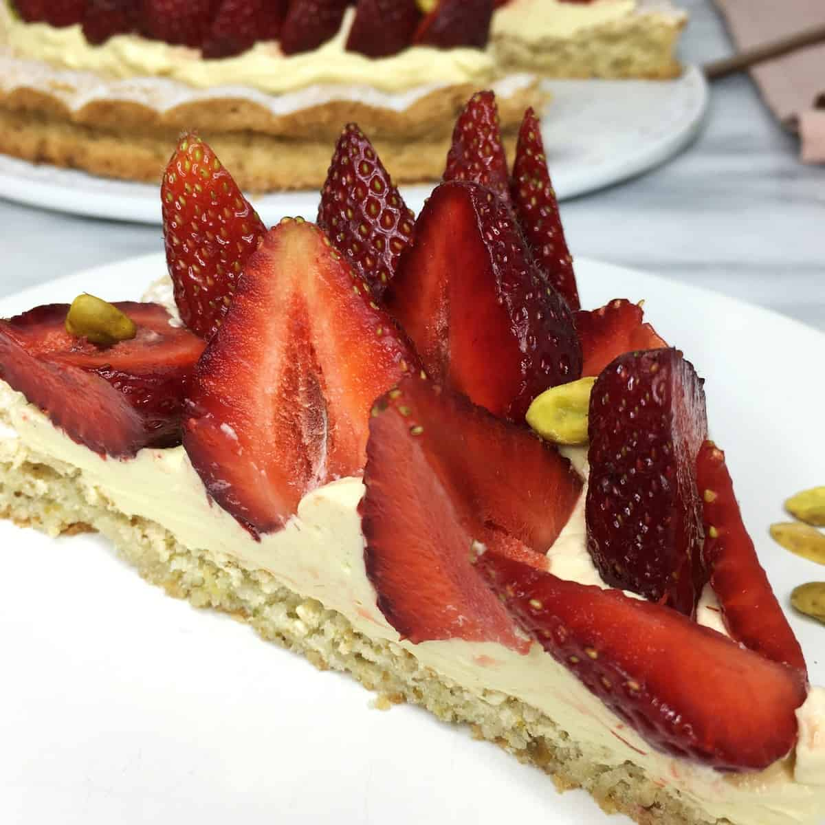 A slice of pistachio dacquoise topped strawberry halves and the rest of the cake on background