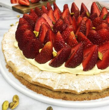 Pistachio dacquoise decorated with fresh strawberries on a white serving platter with berries and flatware on background
