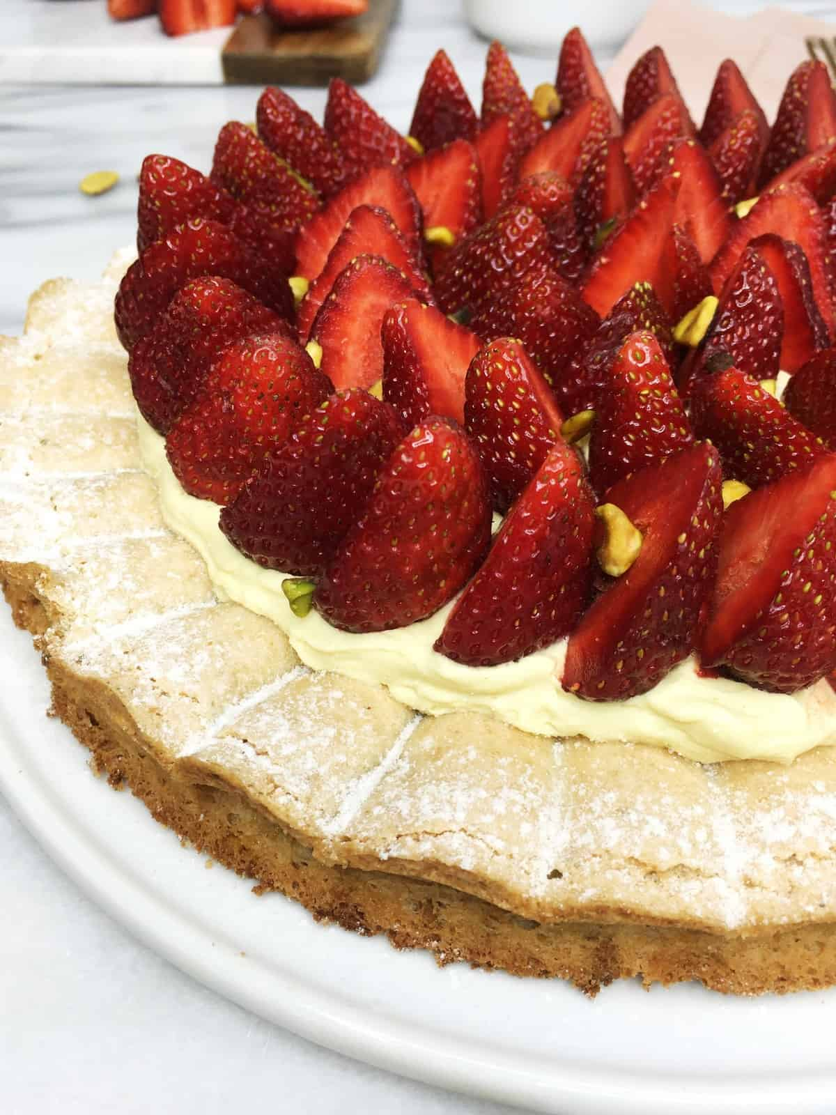 Recipe: Pistachio dacquoise cake topped with cream and strawberries on a white plate