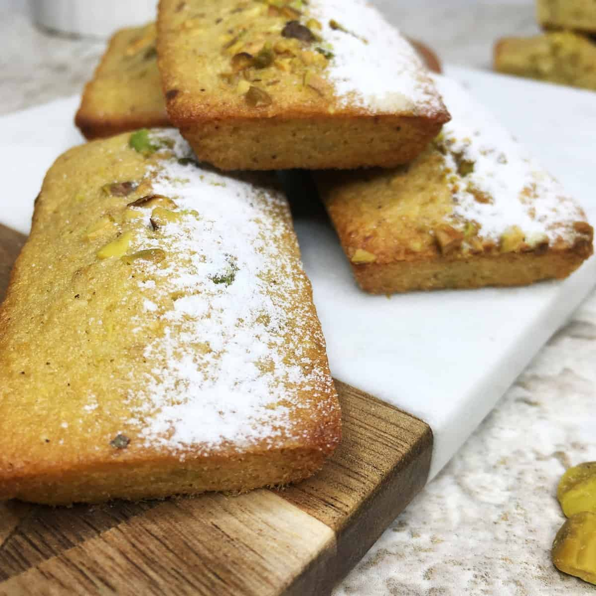 Pistachio financiers sprinkled with icing sugar on a serving board