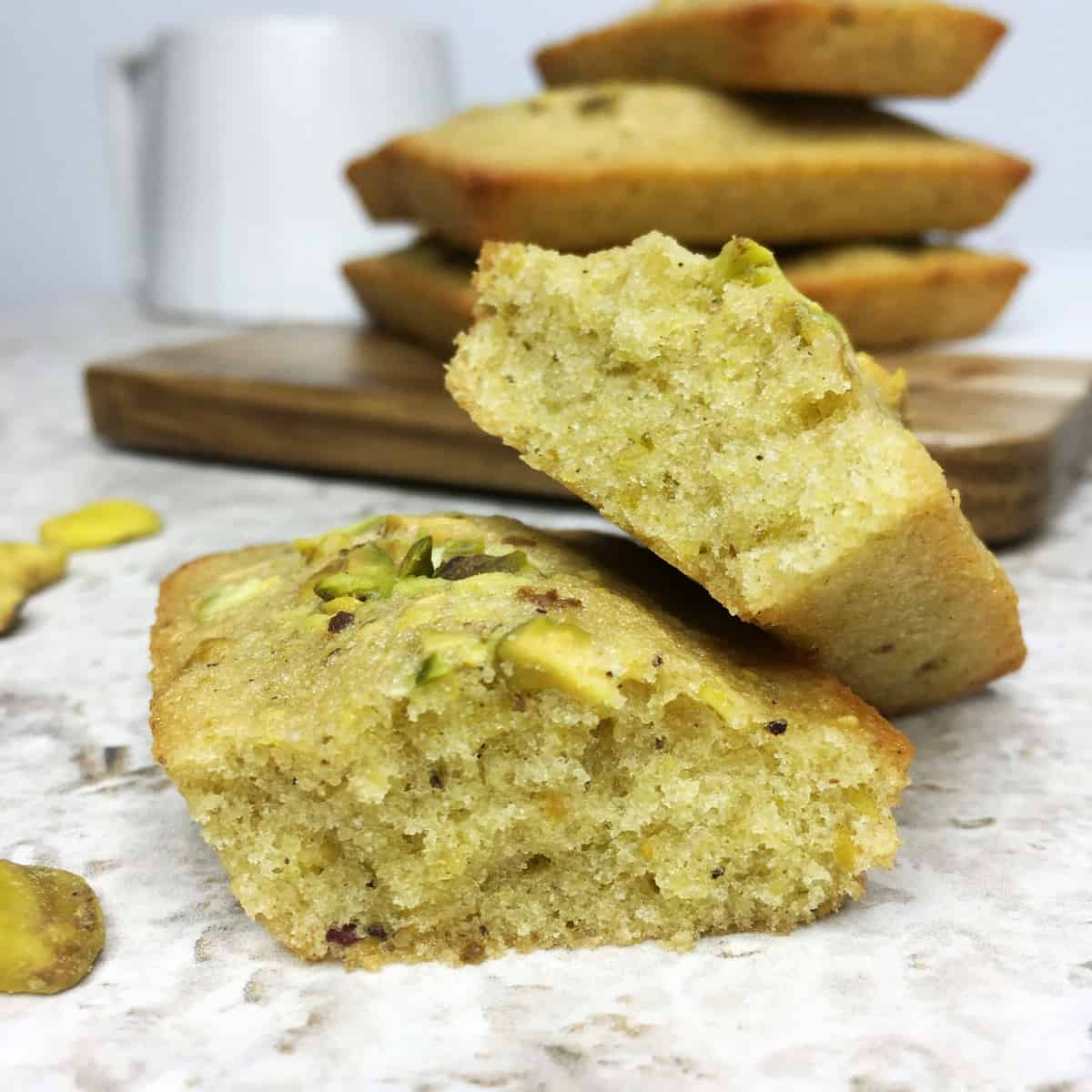 Sliced pistachio financier with the stacked cakes and a cup on a background