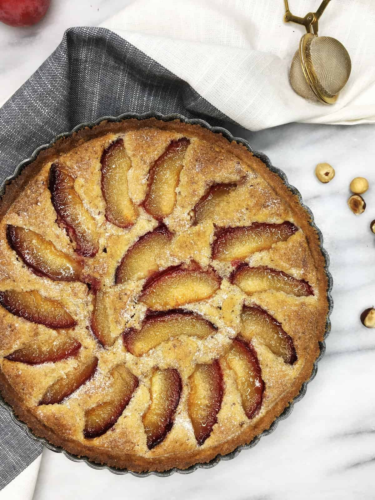 Plum tart in a tart tin with a towel and hazelnuts: Overhead view