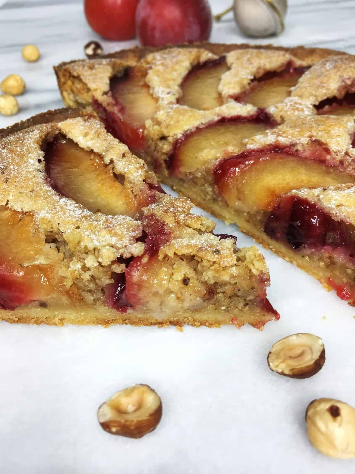 Sliced Plum tart with hazelnuts and plums on background