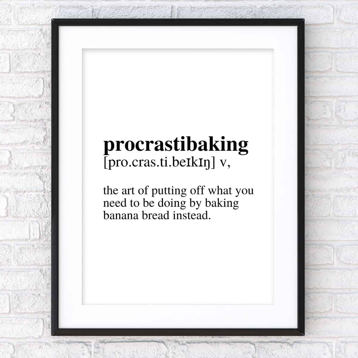 Black frame on the brick wall with the text: Procrastibaking verb definition