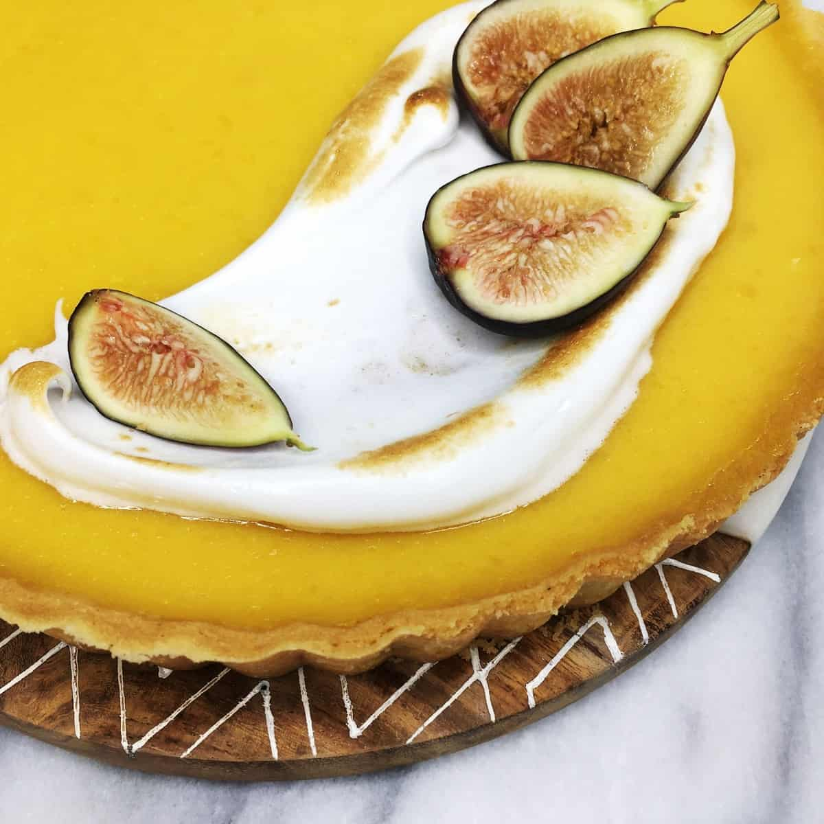 Pumpkin Pie with yellow filling and meringue with fresh figs on top: Closeup