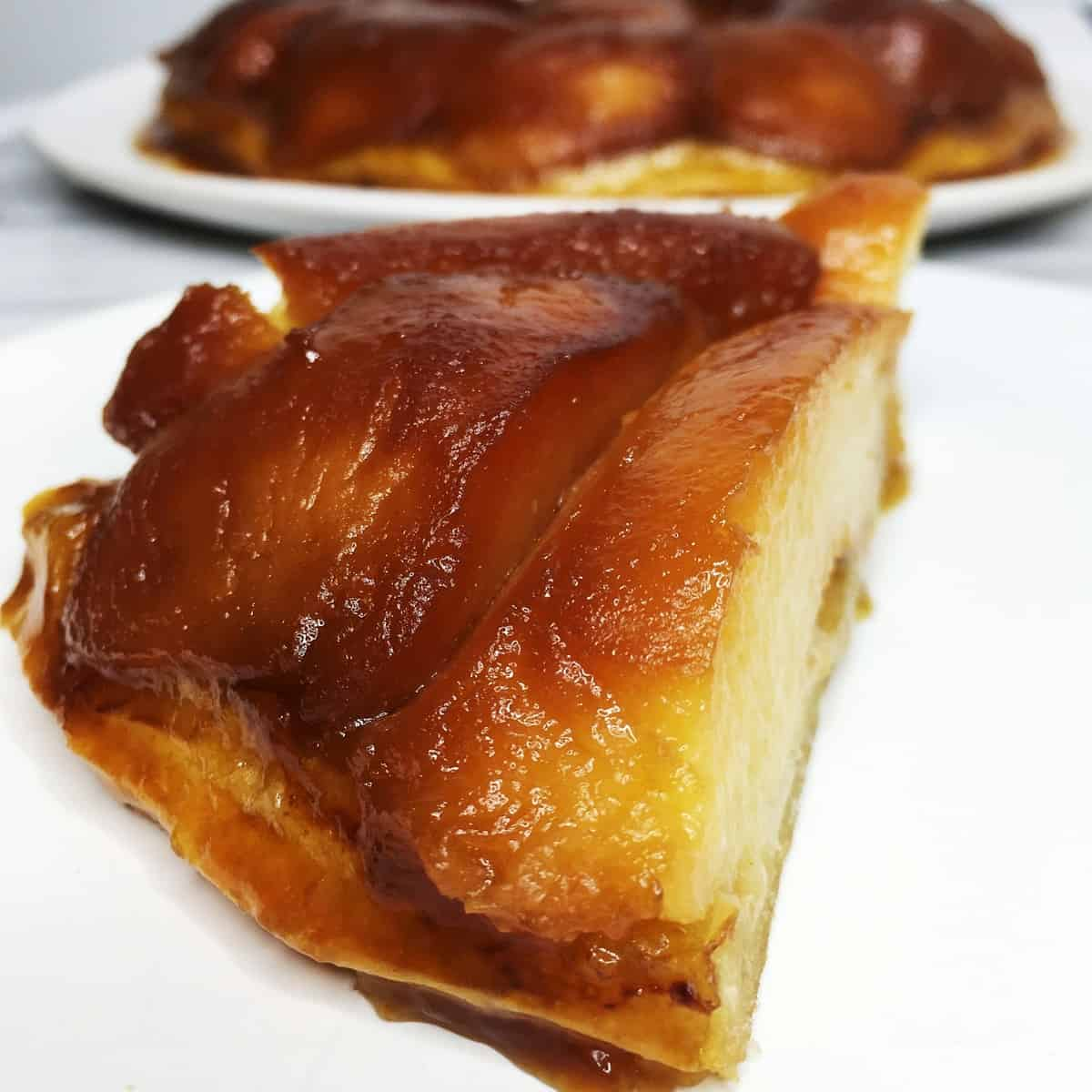A slice of French Quince Tarte Tatin with the rest of the dessert on background