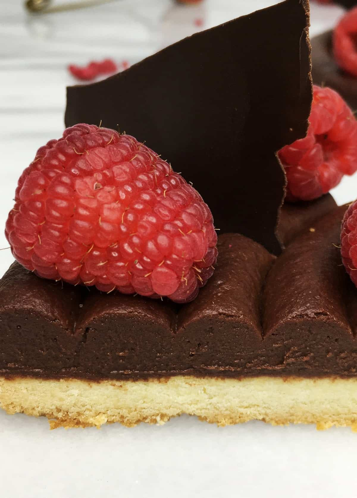 A single slice of the tart topped with chocolate ganache and fresh raspberries: Close up