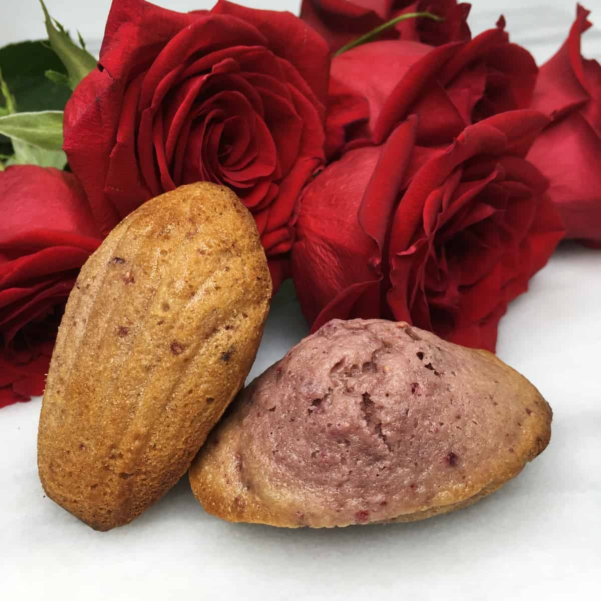 Two raspberry rosewater madeleines with red roses on the background