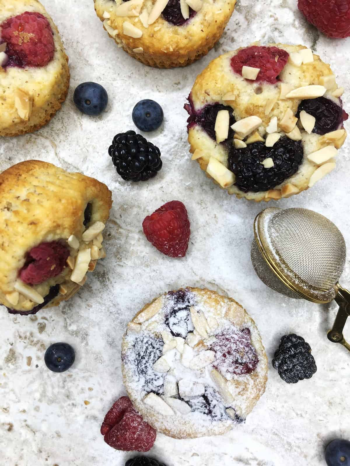 Muffins topped with mixed berries, almonds, icing sugar and fresh red berries around: Overhead view