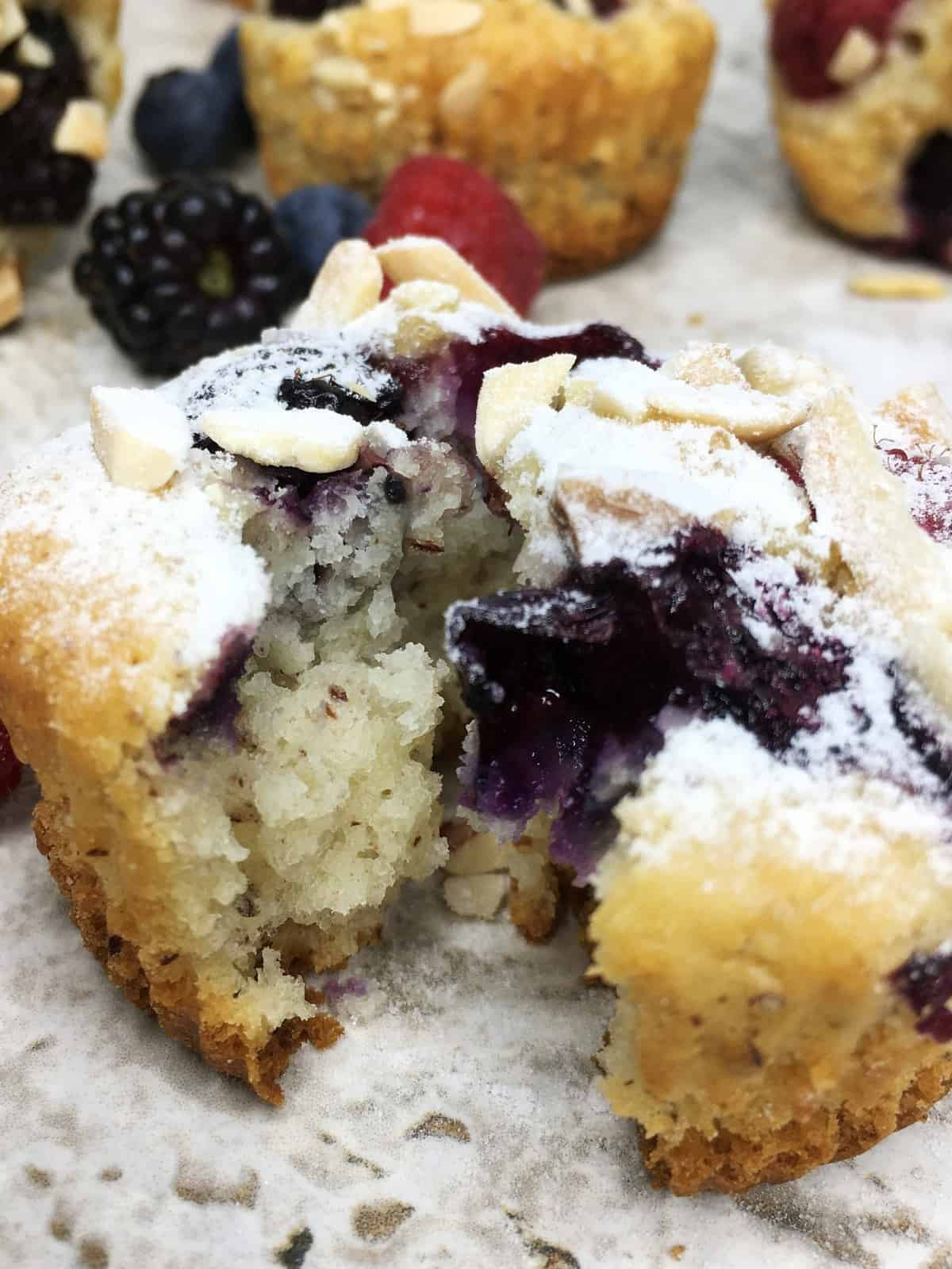 A sliced bite-size muffin topped with berries and sprinkled with icing sugar with other cakes around: Close up