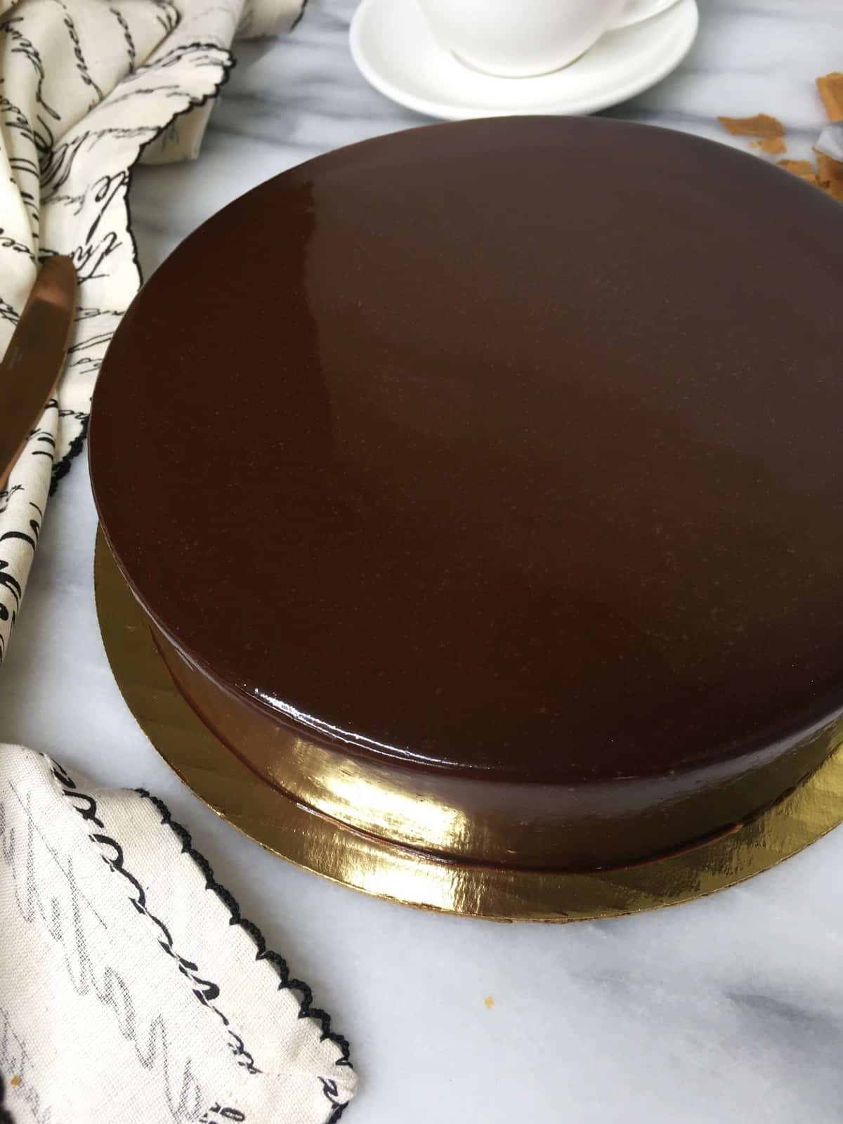 Glazed Royal chocolate cake with a kitchen towel, a knife and a white cup: Overhead view
