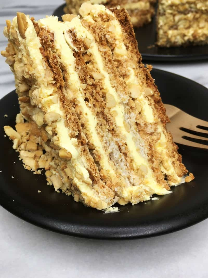 A slice of cake Sans Rival with a fork on a black plate with the remaining cake on background