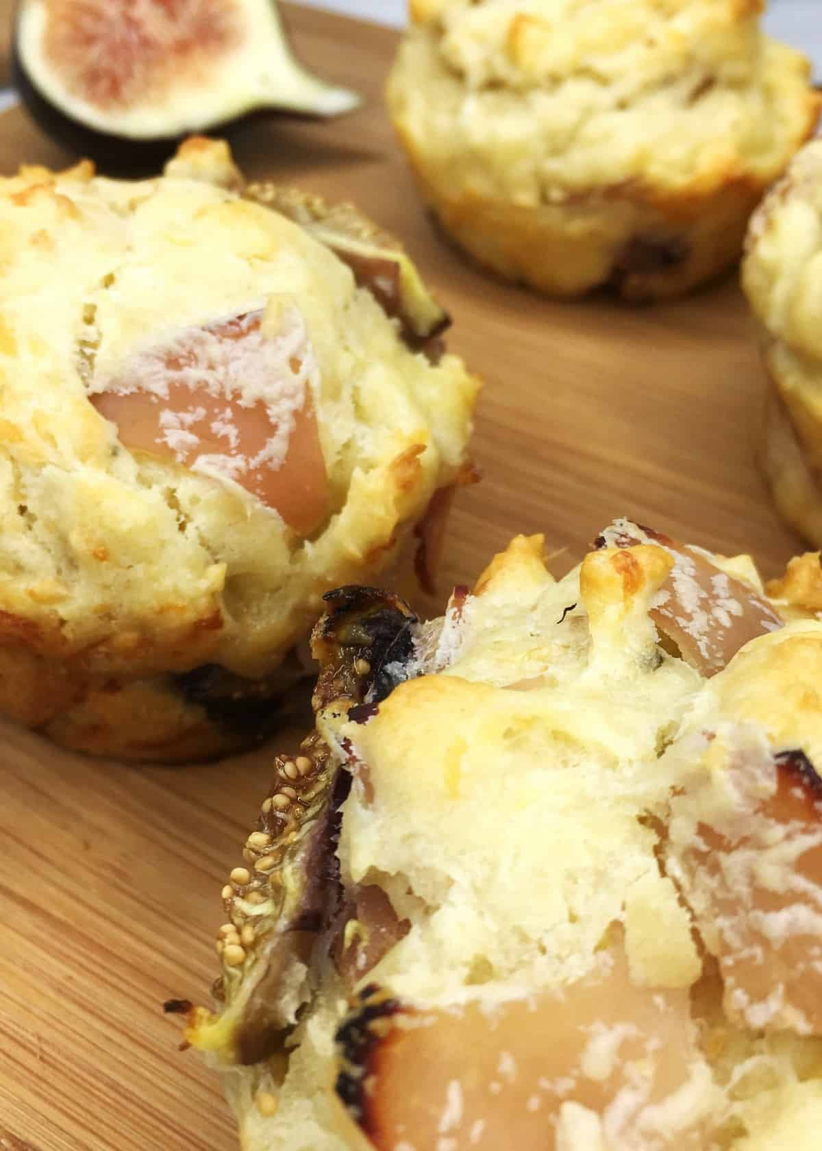 A batch of breakfast muffins filled with ham and figs on a wooden board: Close up