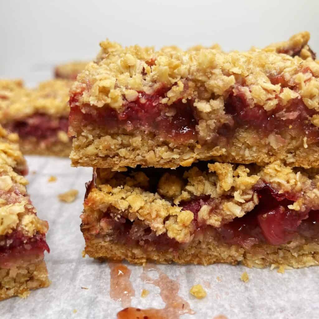 Two stacked strawberry bars made with crumble on parchment: Close up