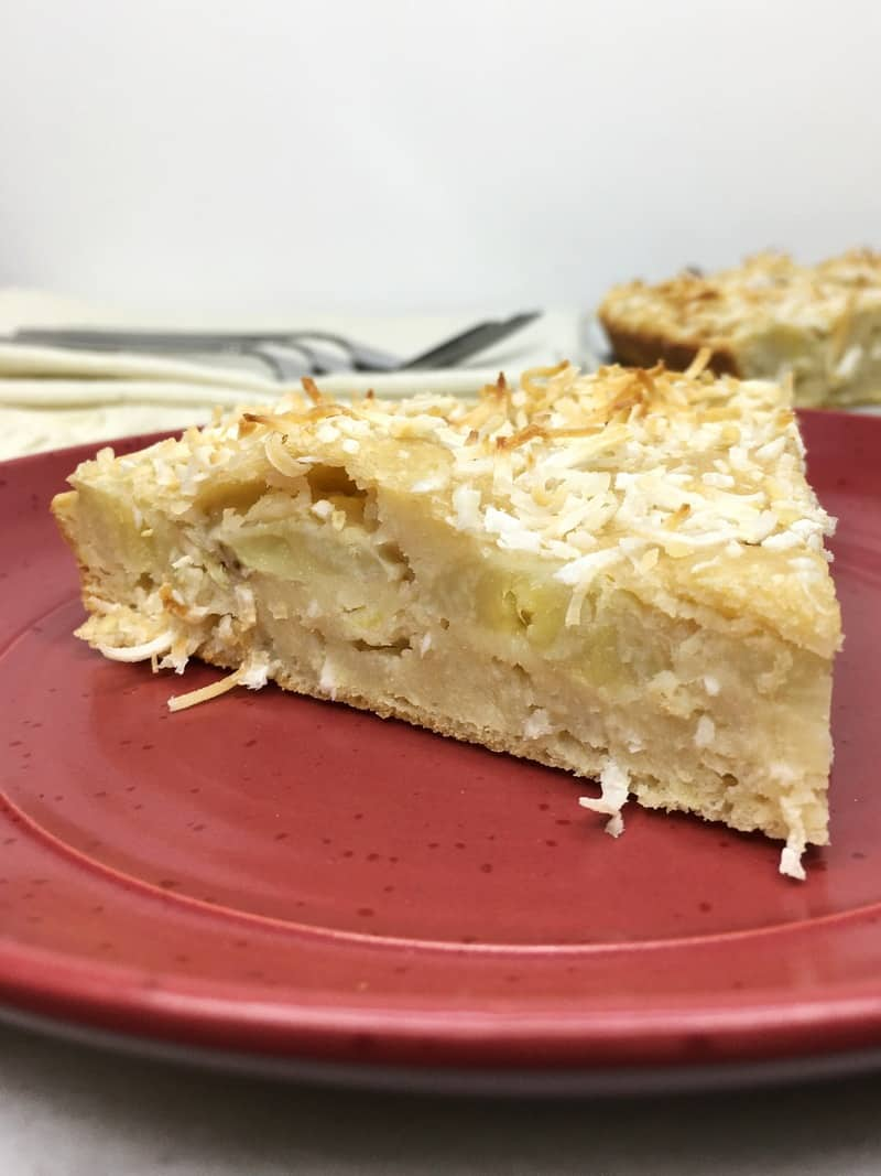 A slice of banana coconut cake on a red plate with forks on background