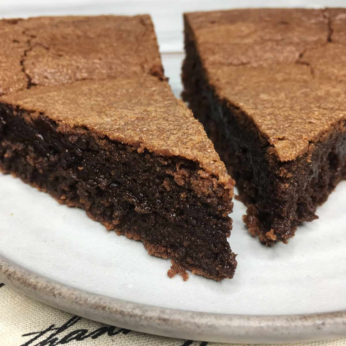 Two slices of Suzy French chocolate cake on a grey plate