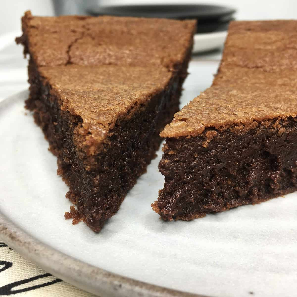 Two slices of Suzy French chocolate cake on a grey plate with other plates on background