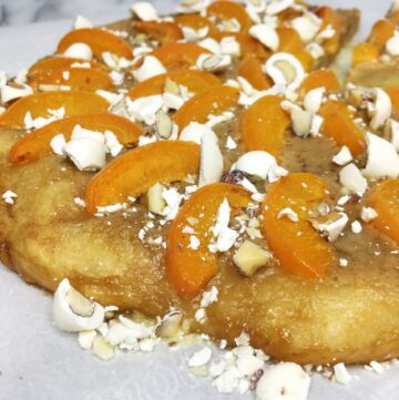 Brioche pizza topped with apricots and yogurt covered almonds on the parchment paper