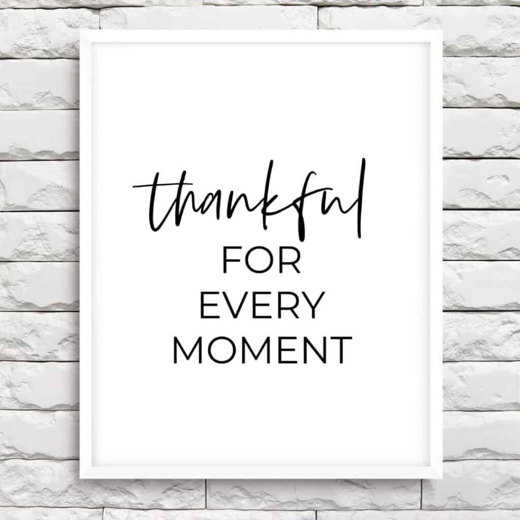 White frame on the brick wall with the text: Thankful for every moment