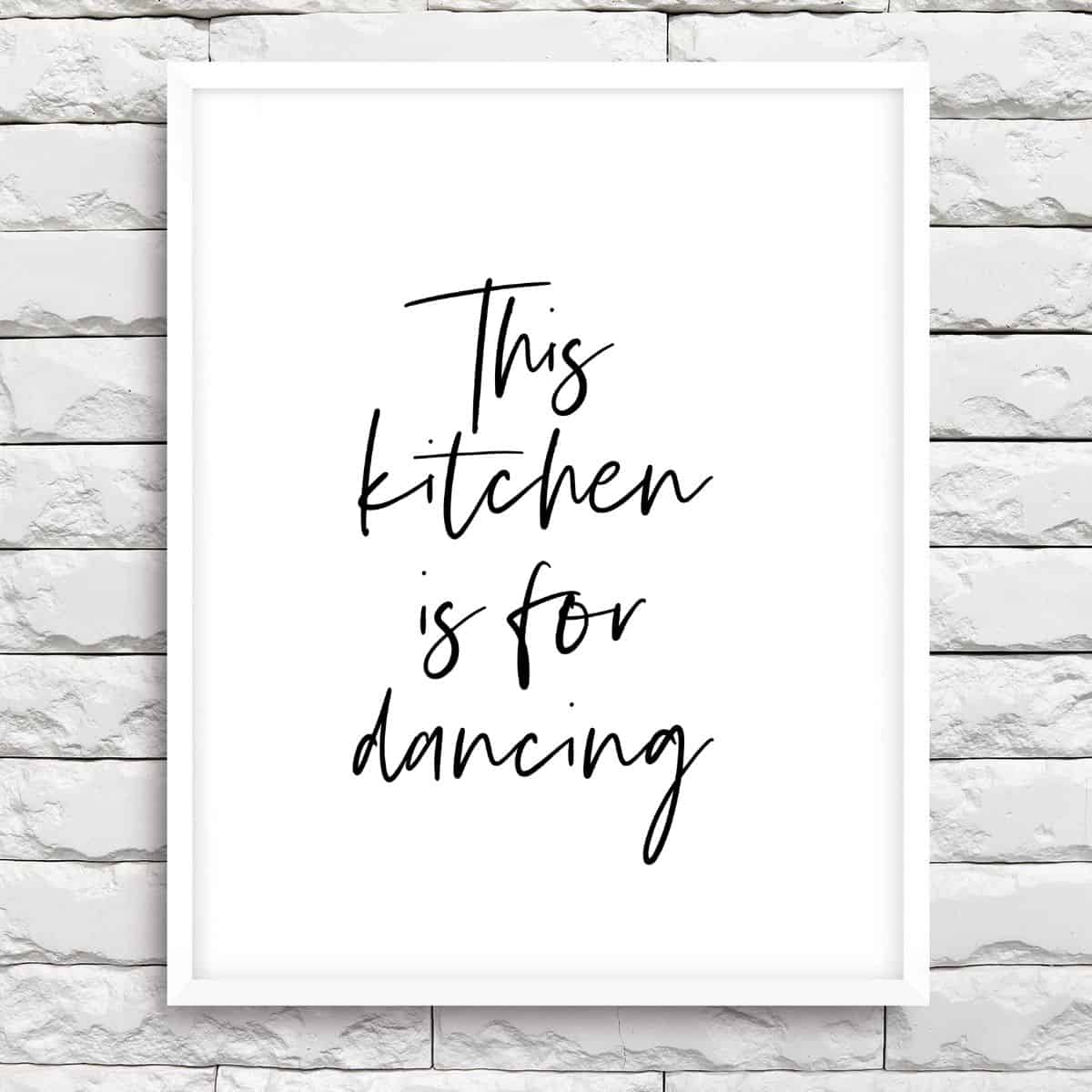 White frame on the brick wall with the text: This kitchen is for dancing